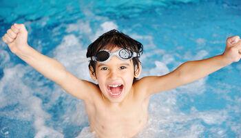 Keyvisual vrij zwemmen - Portret van juichende jongen in het zwembad