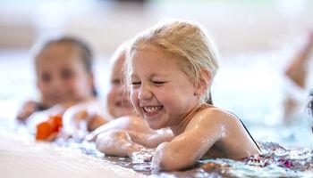 Headerbeeld zwemles voor kinderen - Jonge meisjes giechelend aan de badrand