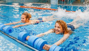 Headerbeeld aquabootcamp - Twee fanatieke meiden met gewichten in het water