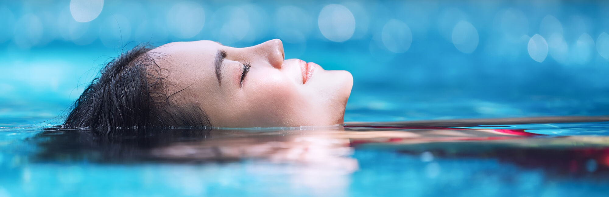 Headerbeeld stiltezwemmen - Vrouw met gesloten ogen drijvend in het zwembad