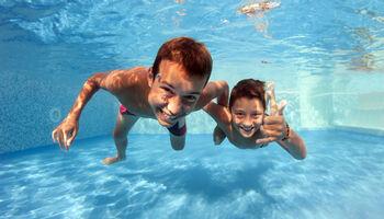 Headerbeeld discozwemmen - Twee kinderen trekken gekke bek onder water